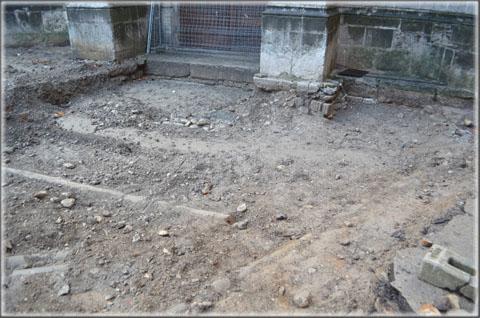 Devant l'entrée principale sous l'ancienne calade on aperçoit le début des fondations des contreforts