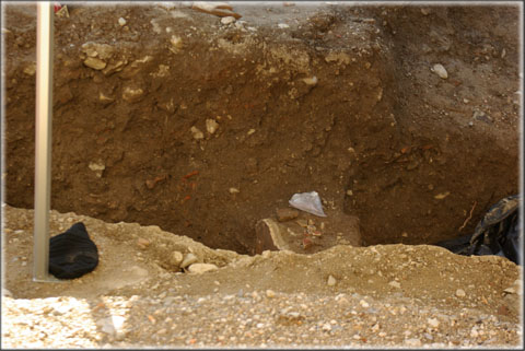 Gros plan sur la zone du sondage profond. Au centre de l'image on distingue le mur romain et sur sa partie gauche, l'enduit peint encore en place