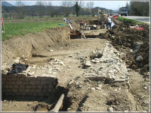 Vue générale du chantier, la première partie fouillée se situe à l'arrière plan, au niveau des deux archéologues. On remarque au premier plan l'ancienne conduite d'eau de Die à Molières qui, lors de sa mise en place, avait relativement peu endommagé les structures, au point qu'aucune découverte n'avait été alors signalée.