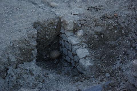 La tranchée révèle la présence d'un mur dont les dimensions, l'orientation et le mode de construction seront consciencieusement relevés. Dans le fond, émergeant de la terre, on distingue le crâne d'un squelette ainsi que différents os longs.