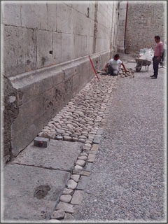 Construction de la calade sur. Au premier plan en bas à gauche, les dalles de fondation d'un contrefort aujourd'hui disparu, similaire à celui qu'on distingue en haut à gauche de l'image.