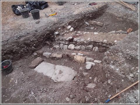 La tranchée (côté Crédit Agricole) : au premier plan tombe en dalles calcaires, devant le mur une autre sépulture (en pleine terre ?) et derrière le mur, tombe en lauzes.
