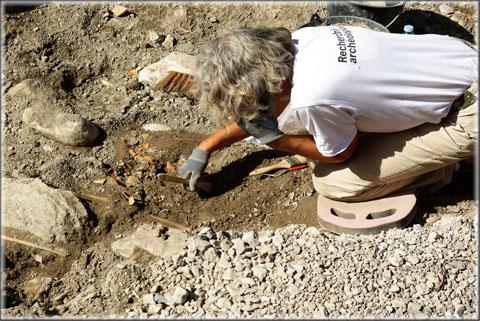Tandis que les archéologues (ici Christine Ronco, responsable du chantier) fouillent les tombes avec minutie afin de ne laisser passer aucun indice.