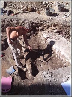 Vendredi 27 septembre : le prélèvement des os d'une sépulture a permis de mettre à jour une nouvelle tombe en lauze, dont le couvercle en lauzes apparait progressivement sous la pelle de l'archéologue. Elle sera fouillée dans le courant de la semaine prochaine.